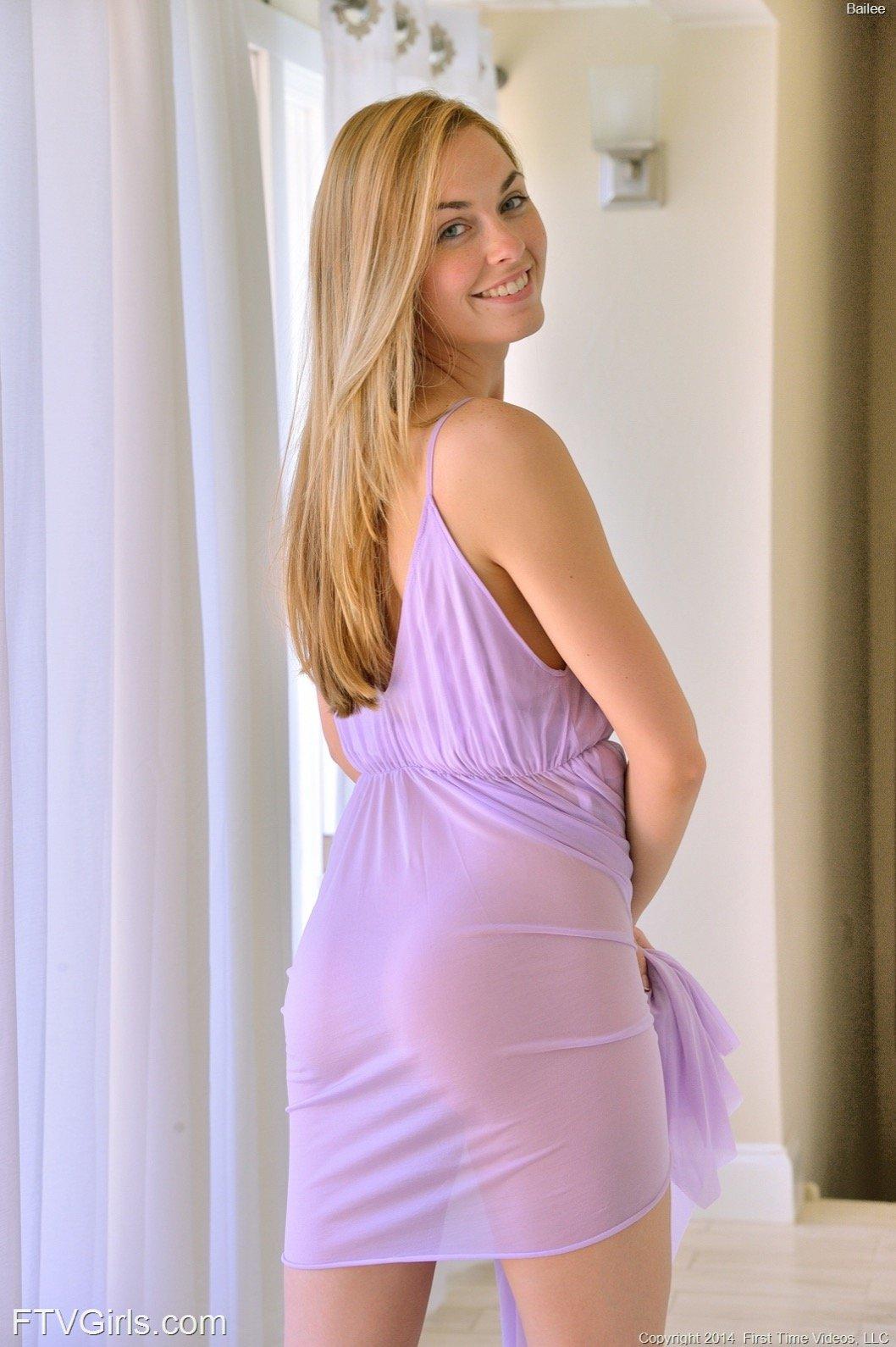 Милая девушка в платье нагибается раком и позирует